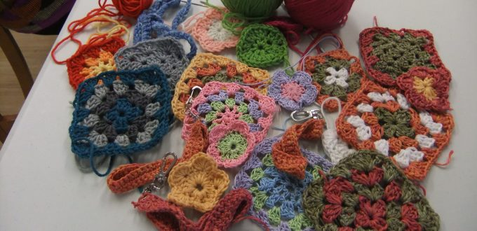 granny squares and flowers crocheted by students on debbie tomkies' beginners crochet workshops